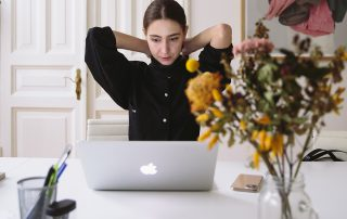 woman sitting with arms behind her heard in front of a counter with a laptop and vase of dried flowers.